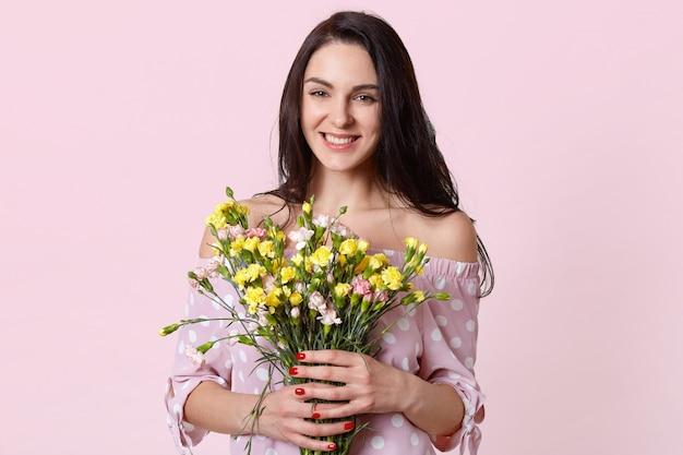Felice donna positiva con i capelli scuri, tiene i fiori in mano, sorride positivamente, gode di una calda giornata primaverile, vestita in elegante abito a pois Foto Gratuite