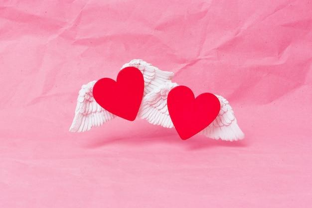 Felice giorno di san valentino banner. un cuore di legno rosso con bianche ali voluminose sale su uno sfondo di carta stropicciata rosa. minimalismo. posto per il testo Foto Premium