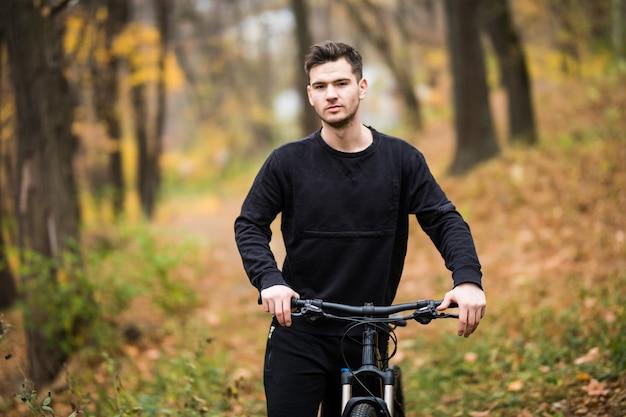 Felice giovane ciclista uomo in sella alla sua bicicletta su un allenamento nella foresta di autunno Foto Gratuite