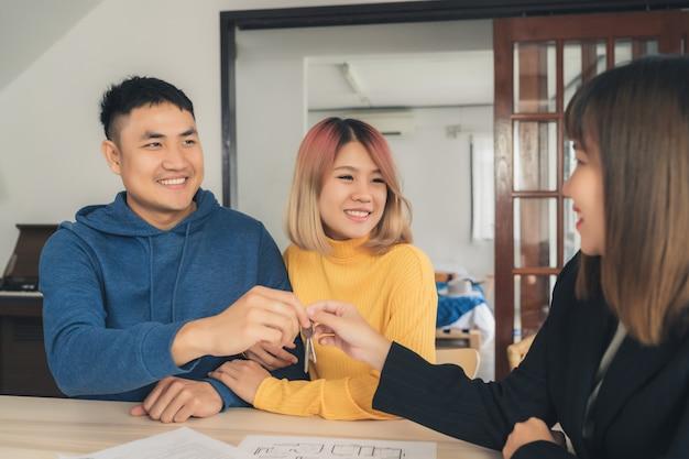 Felice giovane coppia asiatica e agente immobiliare Foto Gratuite