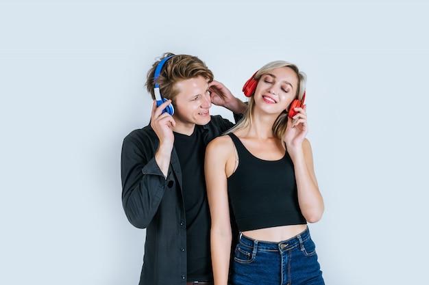 Felice giovane coppia in ascolto musica in cuffia Foto Gratuite