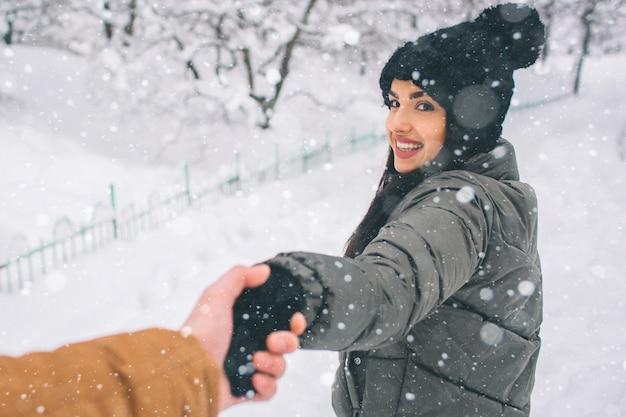 Felice giovane coppia in inverno. famiglia all'aperto. uomo e donna guardando verso l'alto e ridendo. amore, divertimento, stagione e persone - passeggiate nel parco invernale. alzati e tieniti per mano Foto Premium