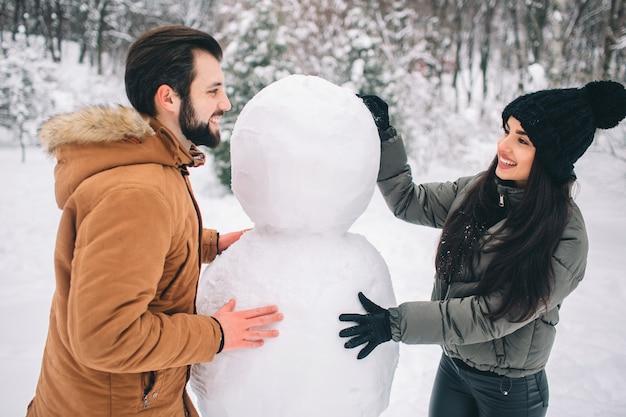 Felice giovane coppia in inverno. famiglia all'aperto. uomo e donna guardando verso l'alto e ridendo. amore, divertimento, stagione e persone - passeggiate nel parco invernale. fare un pupazzo di neve. Foto Premium