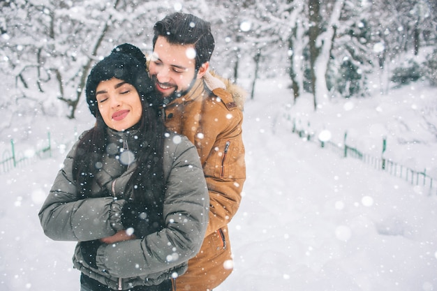 Felice giovane coppia in inverno. famiglia all'aperto. uomo e donna guardando verso l'alto e ridendo. amore, divertimento, stagione e persone - passeggiate nel parco invernale. sta nevicando, si stanno abbracciando Foto Premium