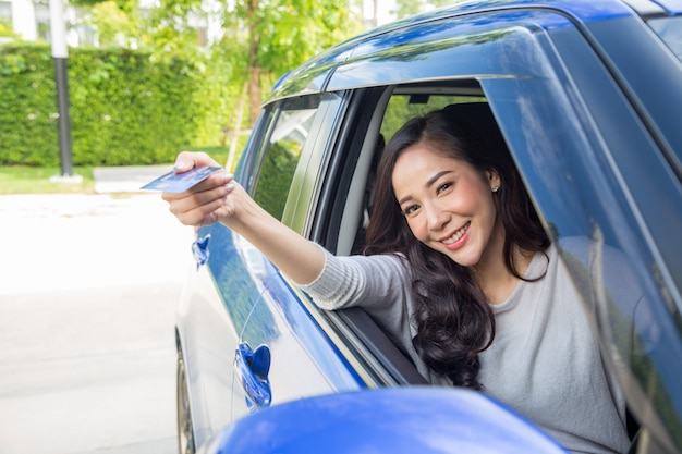 Felice giovane donna asiatica in possesso di carta di pagamento o carta di credito e utilizzato per pagare benzina, diesel e altri carburanti alle stazioni di servizio Foto Premium