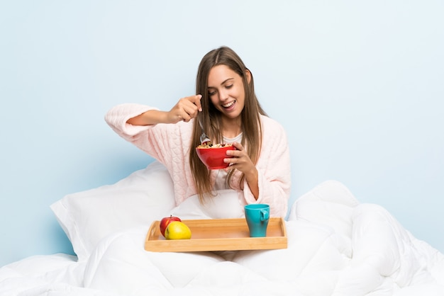 Felice giovane donna in vestaglia con colazione Foto Premium