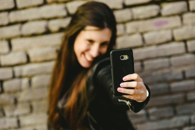 Felice giovane donna millenaria che si fa selfie mentre sogna di flirtare con il ragazzo di cui è innamorata quando carica le foto sui social network. Foto Premium