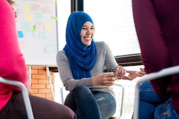 Felice giovane donna musulmana in riunione di gruppo Foto Premium