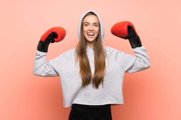Felice giovane donna sportiva rosa con guantoni da boxe Foto Premium