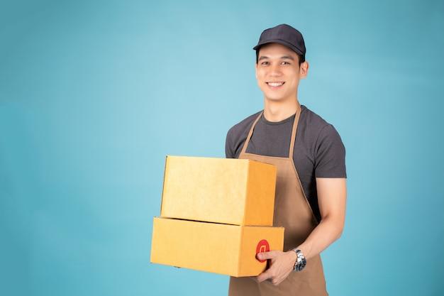 Felice giovane fattorino in berretto nero in piedi con scatola pacco postale Foto Premium