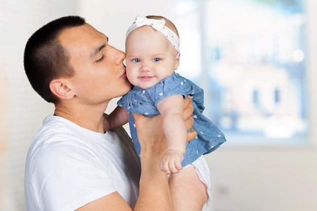 Felice giovane in possesso di un bambino Foto Premium