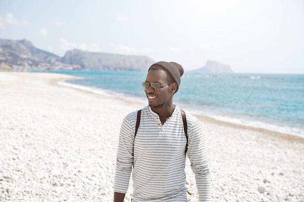 Felice giovane viaggiatore afroamericano in elegante cappello e occhiali da sole con una bella passeggiata lungo la spiaggia, godendo di tempo soleggiato e splendide viste. giovane uomo di colore attraente che posa nel paesaggio del mare Foto Gratuite