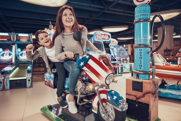 Felice mamma e figlio su moto giocattolo. Foto Premium