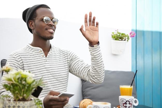 Felice maschio dalla pelle scura che indossa maglietta a maniche lunghe a strisce, cappello e occhiali da sole messaggi online tramite cellulare, agitando la mano mentre vede un amico o chiamando cameriere durante la colazione al caffè Foto Gratuite