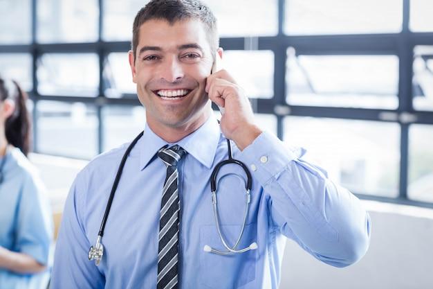 Felice medico al telefono in ospedale Foto Premium