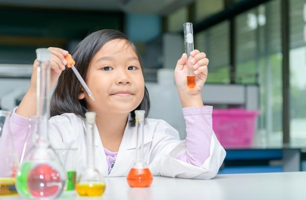 Felice piccolo scienziato in camice da laboratorio facendo esperimento Foto Premium