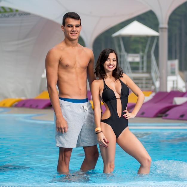 Felice ragazzo atletico e ragazza con una figura perfetta vicino alla piscina sulla località di montagna di lusso con sfondo sfocato Foto Premium