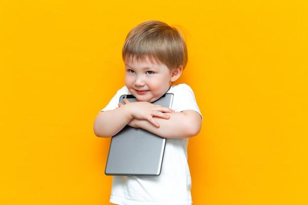 Felice ragazzo carino che abbraccia il suo bel pc tablet, generazione z, bambini che sono nati con la tecnologia Foto Premium