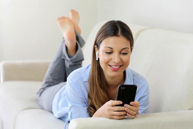 Felice rilassata giovane donna che indossa gli auricolari wireless ascoltando musica sdraiato su un divano nel soggiorno di casa Foto Premium