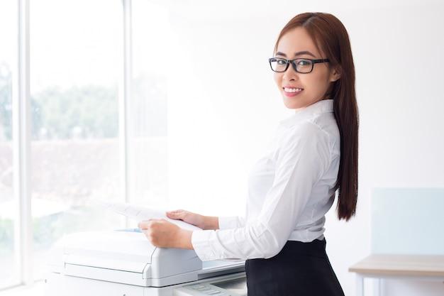 Felice signora asiatica che per mezzo stampante multifunzione Foto Gratuite