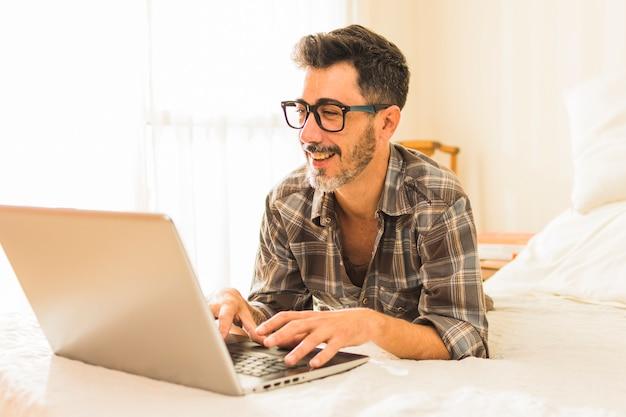 Felice uomo disteso sul letto accogliente utilizzando il computer portatile Foto Gratuite
