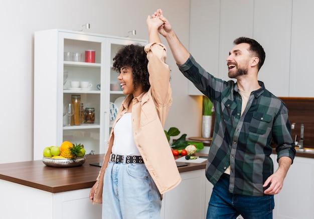 Felice uomo e donna che balla in cucina Foto Gratuite