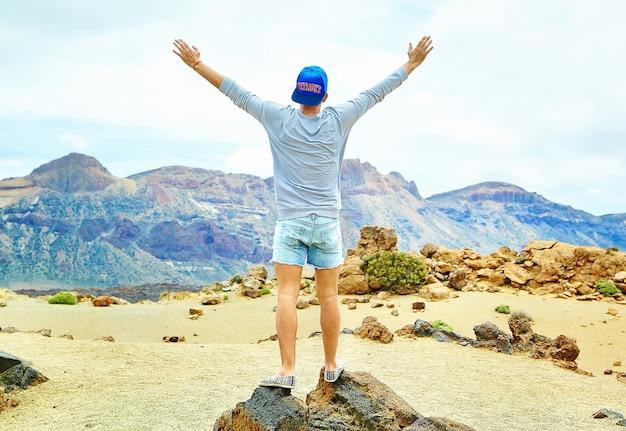 Felice uomo elegante in abiti casual casual in piedi sulla scogliera della montagna con le mani sollevate verso il sole e celebrando il successo Foto Gratuite
