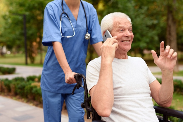 Felice vecchio in sedia a rotelle a parlare su un telefono cellulare Foto Premium