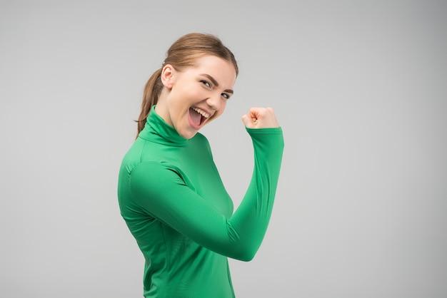 Felicemente giovane donna gladden che esamina la macchina fotografica con cleanch il pugno su e che sorride con la bocca aperta Foto Premium