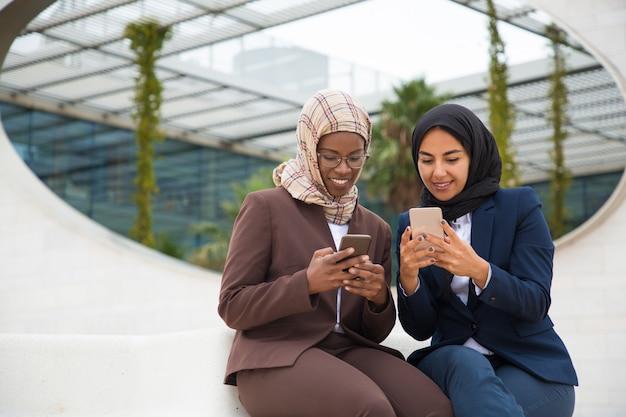 Felici colleghi entusiasti in chat su smartphone Foto Gratuite