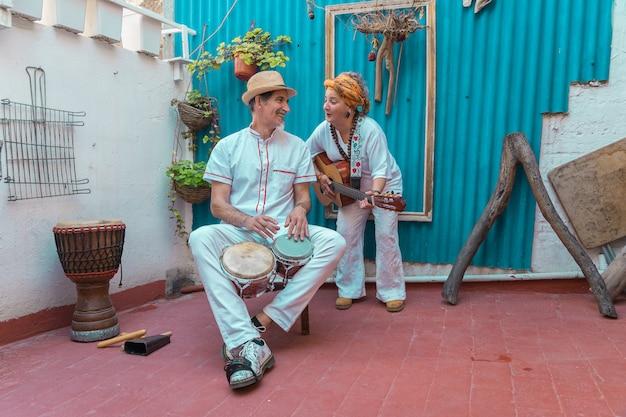 Felici musicisti di strada che suonano musica e cantano per strada a l'avana vecchia Foto Premium