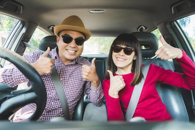 Felicità asiatica delle coppie di vista frontale che si siede in pollice di manifestazione di automobile su. Foto Premium