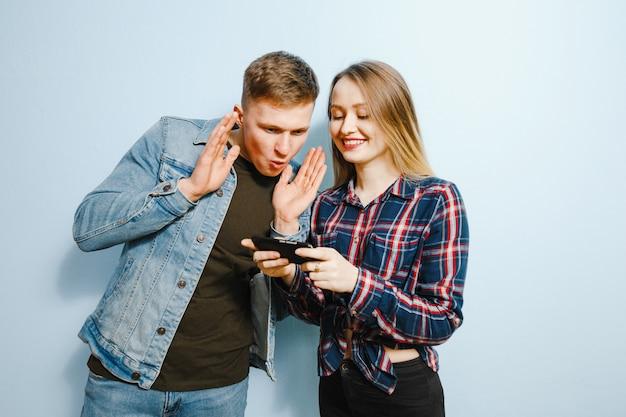 Felicità sul volto di due amici, su sfondo blu, guardando il telefono. Foto Premium