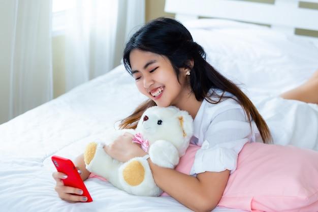 Femmina adolescente sveglia allegra con lo smartphone sul letto Foto Gratuite
