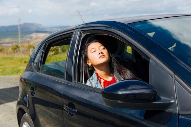 Femmina asiatica che si siede in macchina e che gode del sole Foto Gratuite