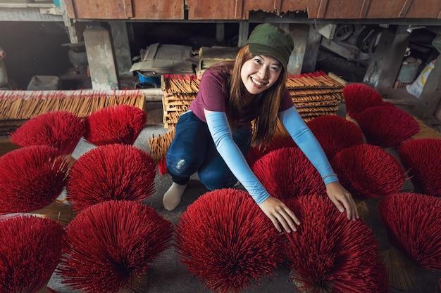 Femmina asiatica del viaggiatore che fa l'insenso rosso tradizionale del vietnam in vecchia casa tradizionale a xuyen lungo, una provincia del giang, concetto tradizionale e della cultura del vietnam Foto Premium