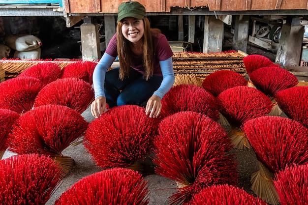 Femmina asiatica del viaggiatore che fa l'insenso rosso tradizionale del vietnam in vecchia casa tradizionale a xuyen lungo, una provincia del giang, vietnam Foto Premium