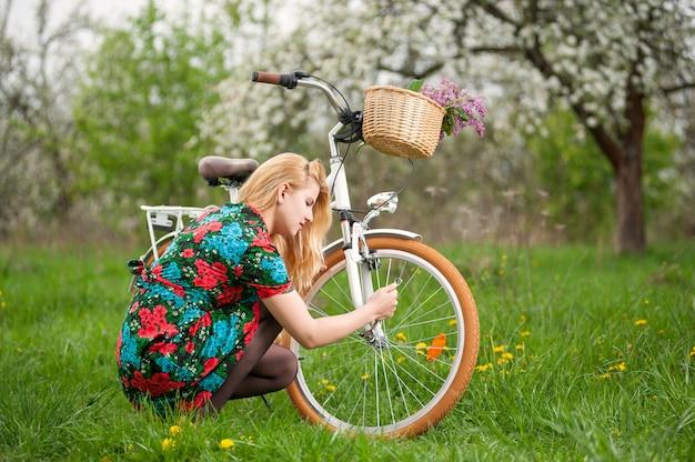 Femmina bionda in vestito fiorito che ripara il suo giardino d'annata bianco della bicicletta in primavera Foto Premium
