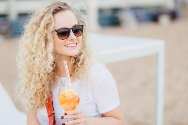 Femmina bionda positiva con i capelli ricci, indossa occhiali da sole, guarda con espressione felice. Foto Premium