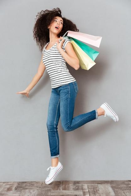 Femmina caucasica del brunette nella posa casuale sulla macchina fotografica con molti pacchetti a disposizione che sono soddisfatti dopo la compera sopra la parete grigia Foto Gratuite