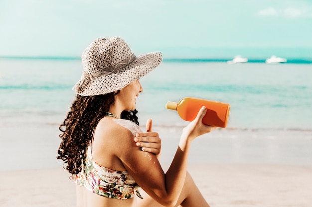 Femmina che applica protezione solare in riva al mare Foto Gratuite
