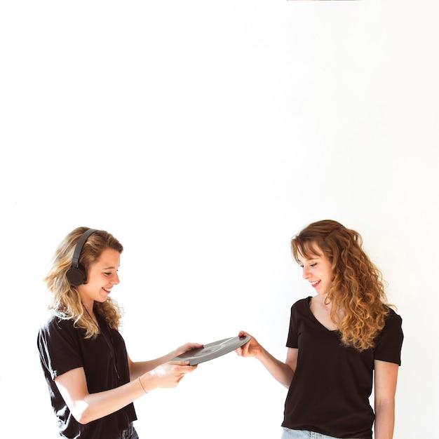 Femmina che dà l'annotazione di vinile a sua sorella che porta cuffia sopra il contesto bianco Foto Gratuite