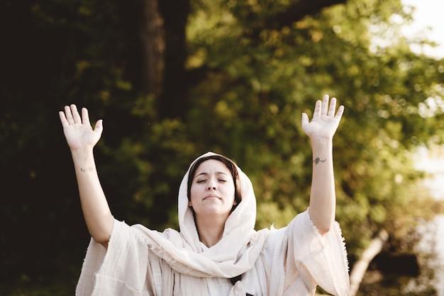 Femmina che indossa un abito biblico con le mani verso il cielo Foto Gratuite