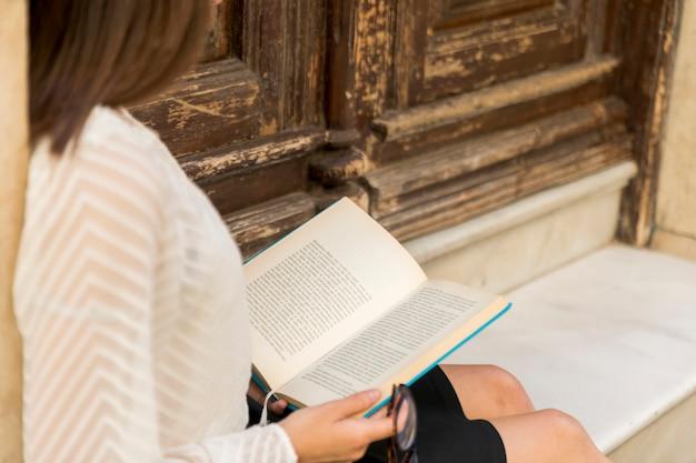 Femmina che legge vicino a porte in legno Foto Gratuite