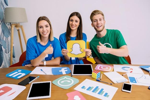 Femmina che tiene logo youtube con i suoi amici che mostrano il segno thumbup Foto Gratuite