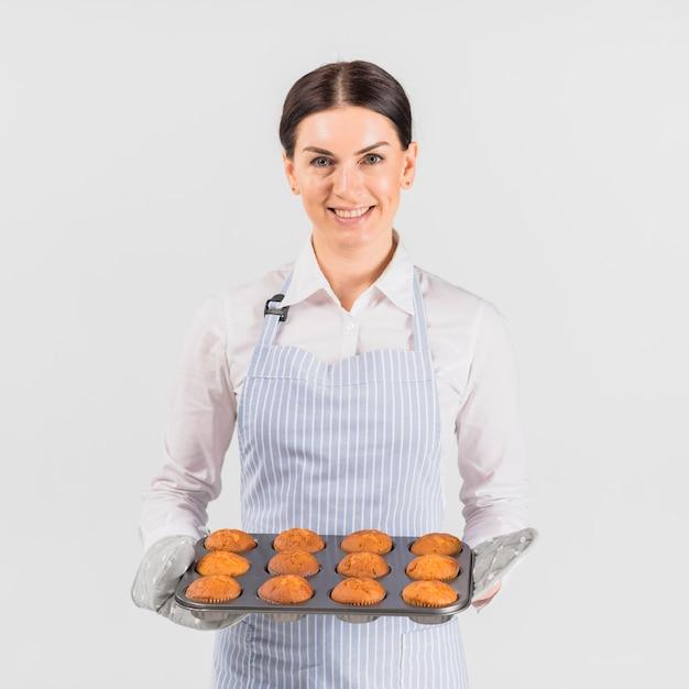 Femmina del cuoco unico di pasticceria che sorride con la latta del muffin Foto Gratuite