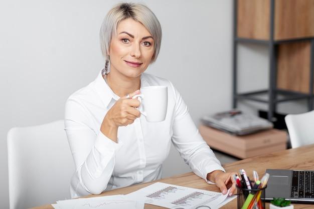 Femmina dell'angolo alto al caffè bevente dell'ufficio Foto Gratuite