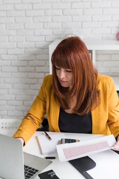 Femmina dell'angolo alto al lavoro d'ufficio Foto Gratuite