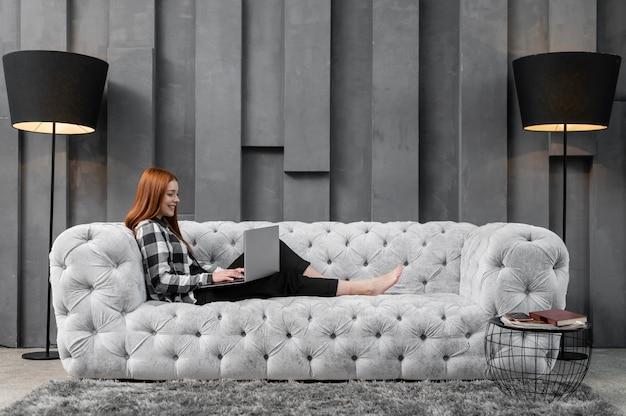 Femmina della foto a figura intera che si rilassa sullo strato Foto Gratuite