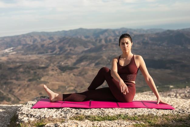 Femmina di vista frontale che si distende dopo la pratica di yoga Foto Gratuite